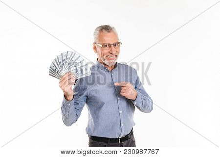 Old smiling grey-haired man in eyeglasses pointing at dollars holding in hand isolated over white