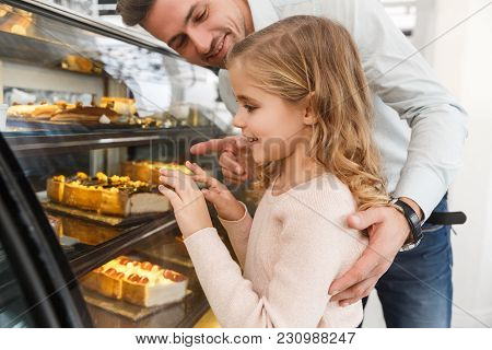Father And Cute Little Daughter Choosing Cake On Display At Cafe