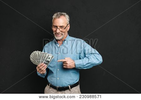 Image of caucasian middle aged man 60s with gray hair pointing finger on money prize holding lots of dollar banknotes isolated over black background