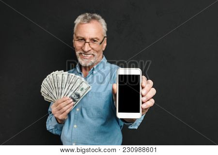 Photo of content retired man 60s with gray hair holding fan of money dollar cash and demonstrating cell phone on camera isolated over black background