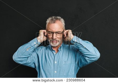 Image of intelligent gentleman 50s wearing businesslike outfit covering ears due to annoying noise or interlocutor isolated over black background