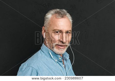 Portrait of handsome mature man 60s with gray hair looking on camera while listening to music via white earphones isolated over black background