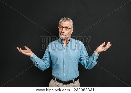 Image of intelligent gentleman 50s wearing businesslike outfit throwing up hands in surprise and expressing helpless isolated over black background