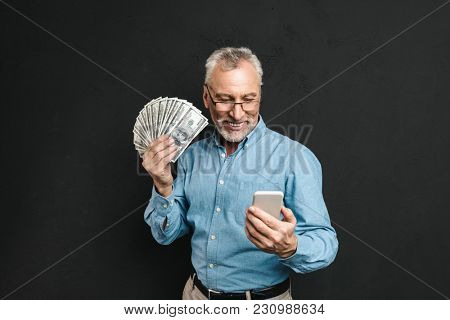 Image of caucasian elderly man 70s with gray hair holding mobile phone and lots of money dollar currency isolated over black background