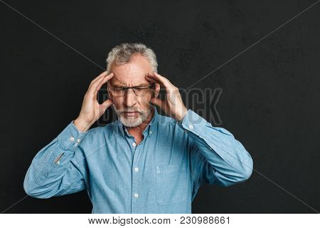 Image of mature man 60s with grey hair and beard suffering from migraine and rubbing temples due to headache isolated over black background