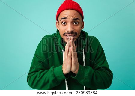 Portrait of a young afro american man in hat begging for something isolated over blue background