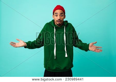 Portrait of a frustrated young afro american man in hat gesturing with hands isolated over blue background