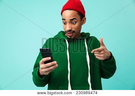 Portrait of a shocked young afro american man in hat pointing finger at mobile phone isolated over blue background
