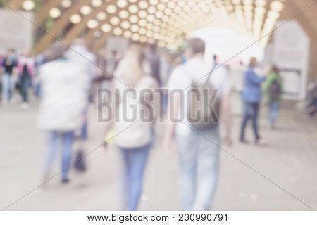 Walking Happy Young Couple With Backpacks. Blurred Abstract Image For Creative Light Background, Pan