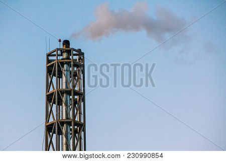 Atmospheric Air Pollution From Industrial Smoke. Plant Pipes With Smoke On Background Of Sunset Sky.