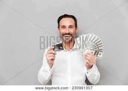 Portrait of a happy mature man dressed in shirt holding credit card while standing and showing money banknotes over gray background