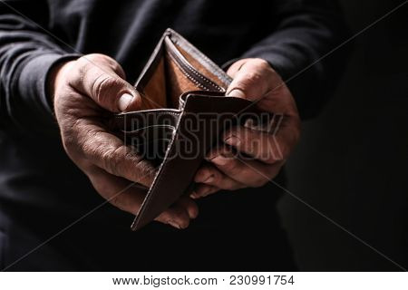 Poor man showing his empty wallet on black background