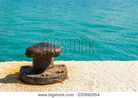 Rusty Bollard With Blue Sea In Background