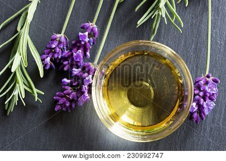Lavender Essential Oil In A Bowl With Fresh Lavender Twigs, Top View
