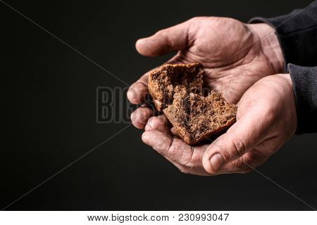 Poor man holding pieces of bread on dark background