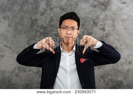 Portrait of a disappointed young asian man dressed in suit showing thumbs down gesture over gray background