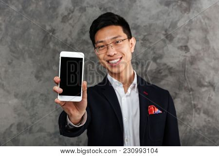 Portrait of a confident young asian man dressed in suit showing blank screen mobile phone over gray background