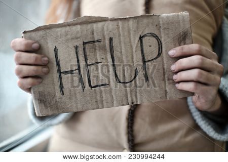 Poor woman holding piece of cardboard with word HELP, closeup