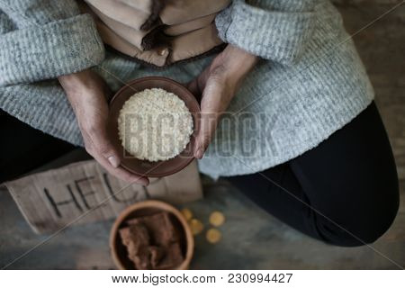 Poor woman holding bowl with rice, closeup