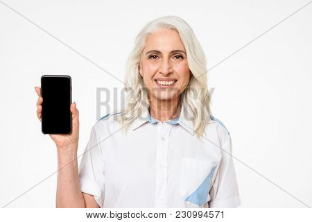 Picture of adult woman with grey hair smiling and doing commercial with presenting mobile phone isolated over white background