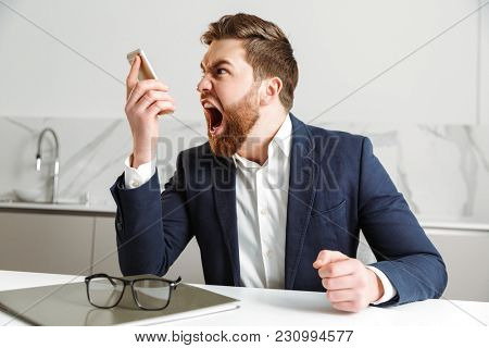 Portrait of an angry young businessman dressed in suit yelling at mobile phone while sitting at the table indoors