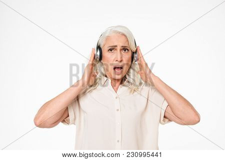 Photo of retired female pensioner with gray hair listening to music using wireless headphones and expressing concern or irritation isolated over white background