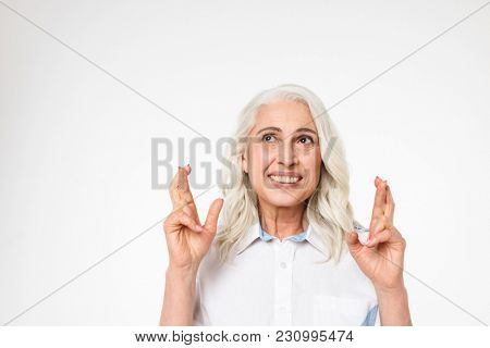 Senior caucasian woman thinking about something pleasant and making wish with crossed fingers isolated over white background
