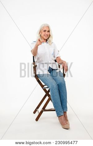 Full length portrait of joyful mature woman 70s with gray hair sitting on wooden chair and pointing finger on camera isolated over white background