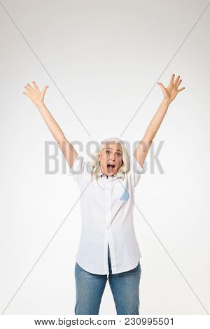 Beautiful female pensioner 60s with gray hair raising her arms and screaming like happy woman isolated over white background