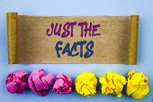 Handwriting text showing Just The Facts. Concept meaning Truth Fact Accuracy Honest Concept For Factual Actual  written tear sticky note Paper the blue background Folded paper poster