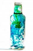 a bottle full of swirling colorful water on a white background. poster