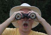 Male bird watcher looking at a Bald Eagle through binoculars poster