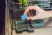 Dishwasher with dirty dishes. Powder, dishwashing tablet and rinse aid. Washing dishes in the kitchen. poster