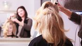 Beautiful smiling girl with blond wavy hair by hairdresser. Hairstylist combing female client young woman in hairdressing beauty salon. Hairstyle. poster