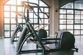 Close up view of elliptical fitness crosstrainer machines in fitness center. Perfect for any fitness, training or athletic related purposes poster