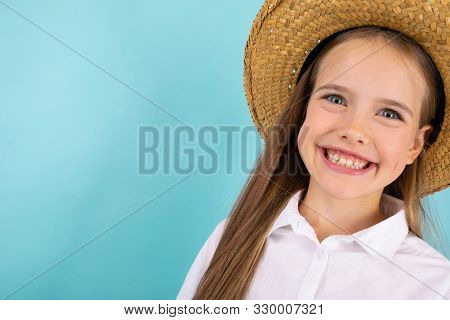 A Teenage Girl With Grey Eyes, Nice Smile And With A Hat Smiling Isolated On Blue Background.