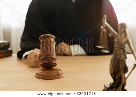 Justice And Law Concept. Male Judge Take Judge Hammer And Judge The Case In A Courtroom.
