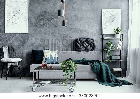 White Pillow On Black Metal Chair Next To Grey Sofa With Pillow In Dark Living Room Interior With Ma