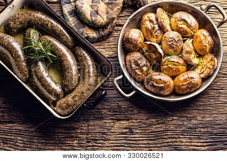 Roasted Sausages In Pan With Rosemary And Potatoes.. Traditional European Food Bratwurst Jaternice O