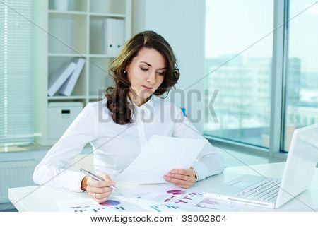 Business lady looking through the papers and taking notes