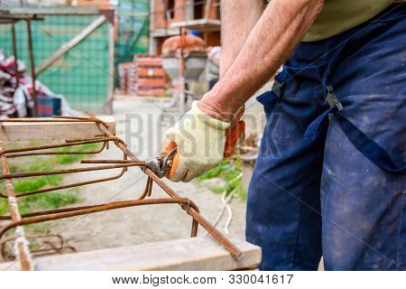 Worker is tying rebar with wire using pliers, to make a reinforcing frame for concrete beam. poster