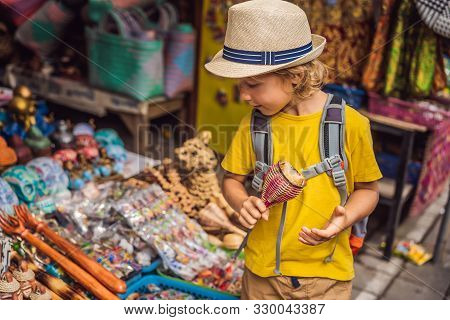 Boy At A Market In Ubud, Bali. Typical Souvenir Shop Selling Souvenirs And Handicrafts Of Bali At Th