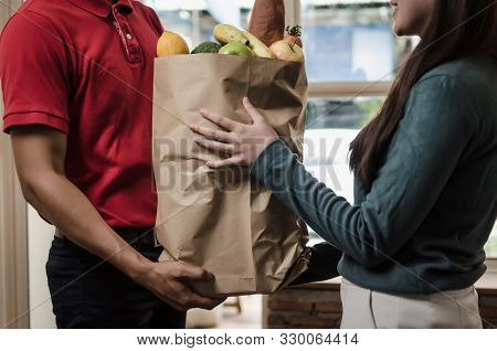 Smart Food Delivery Service Man In Red Uniform Handing Fresh Food To Recipient And Young Woman Custo