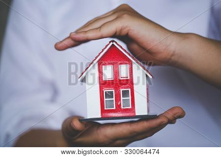 Home Protection Concept The Businessman's Hand Protects The House. Protecting Gestures And Symbols O