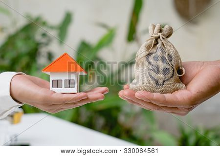 House And Coins In The Hands Of Investors.orange Roof House.save Money For Buying A New Home And Bor