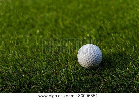 Golf Ball On The Green,green Grass With Golf Ball Close-up In Soft Focus At Sunlight. Sport Playgrou