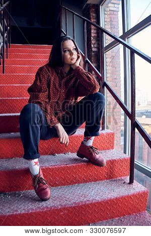 Young Girl Is Sitting On The Red Stairs. Cocky Teen Millennial