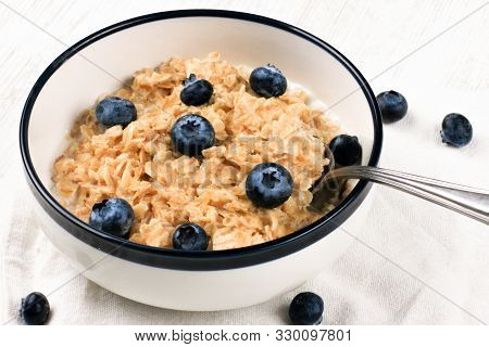 Oatmeal With Fresh Blueberries. Diet Food - Oatmeal Porridge In A Plate With A Spoon.
