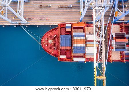 Large Container Ship Loads Cargo In Logistic Port With Crane. Concept Import Export Business. Aerial