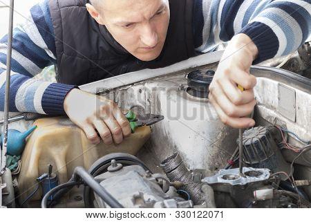 Car Mechanic Holds A Screwdriver And Adjusts Carburetor